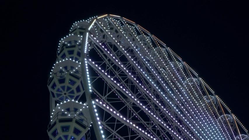 Night view of the ferris wheel. Bright multi-colored lights. Amusement park. | Shutterstock HD Video #1037186369