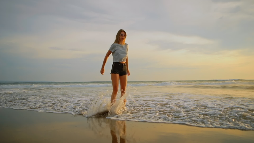 Young female felling fun and free and jumping barefoot on beach at sunset. Carefree girl on tropical beach runs into refreshing sea at golden sunrise. Happy tourist woman on summer vacation. | Shutterstock HD Video #1037190428