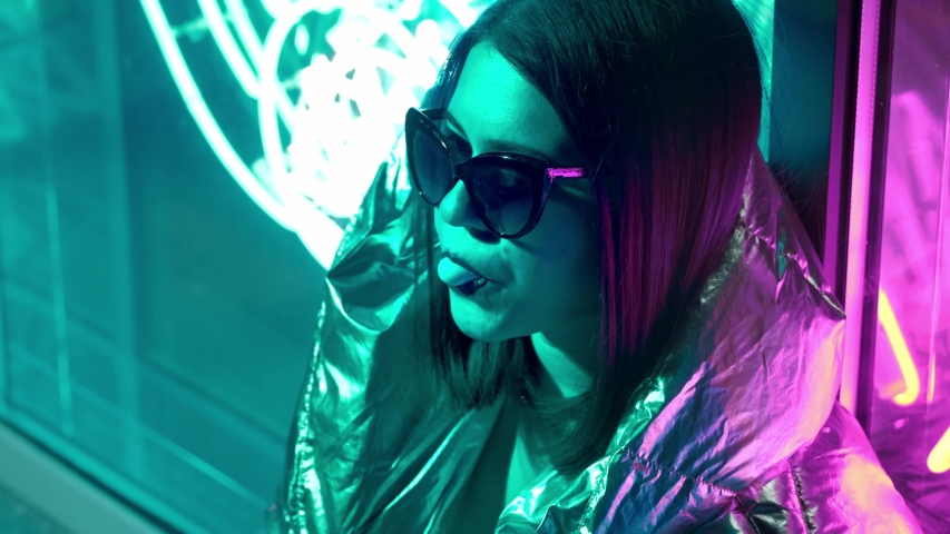 Young fashion teen girl in fur glasses blowing bubble gum illuminated with street neon blue pink sign, beautiful millennial woman in trendy night light glow back to 80s concept. | Shutterstock HD Video #1037199242