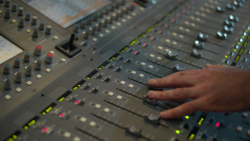 Close-up of a mixing console, the hand adjusts the faders. Sound director works in the studio. Professional recording studio. Recording Concept. Royalty-Free Stock Footage #1037201594