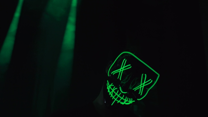 a man performs on stage in a mask. It glows green. Ananimus.