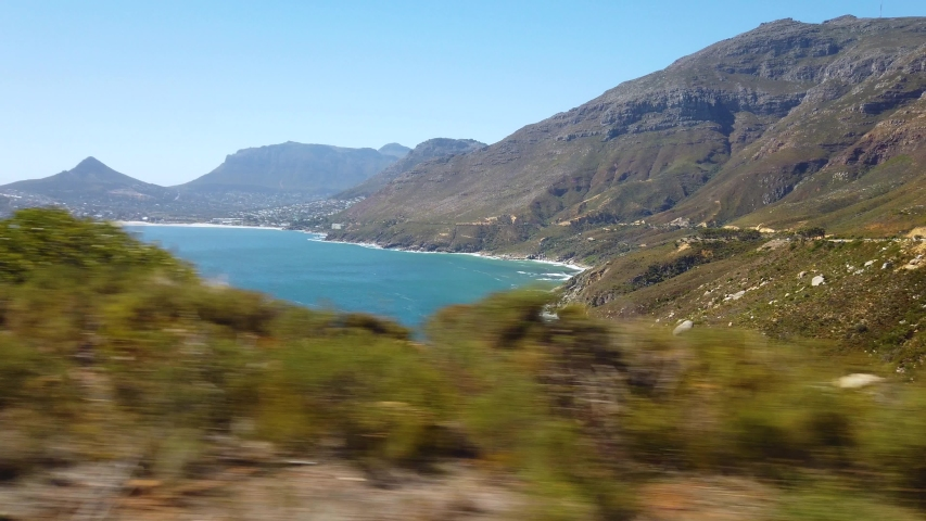 POV footage from a car ride along the hilly shoreline near Cape Town, South Africa. Camp's Bay and Lion's Head visible.