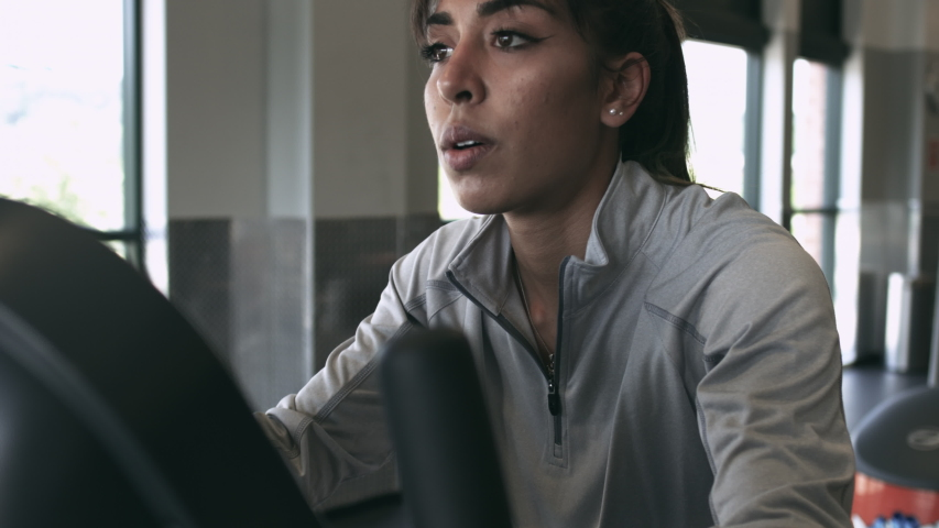 Latina millennial using her phone while on an exercise bike at the gym stabilized shot in 4K UHD | Shutterstock HD Video #1037205488