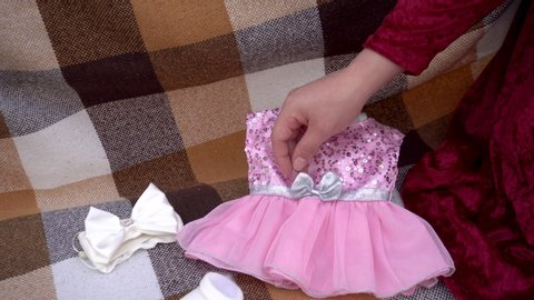 Young pregnant woman touches baby clothes. Woman in a red dress plays with booties