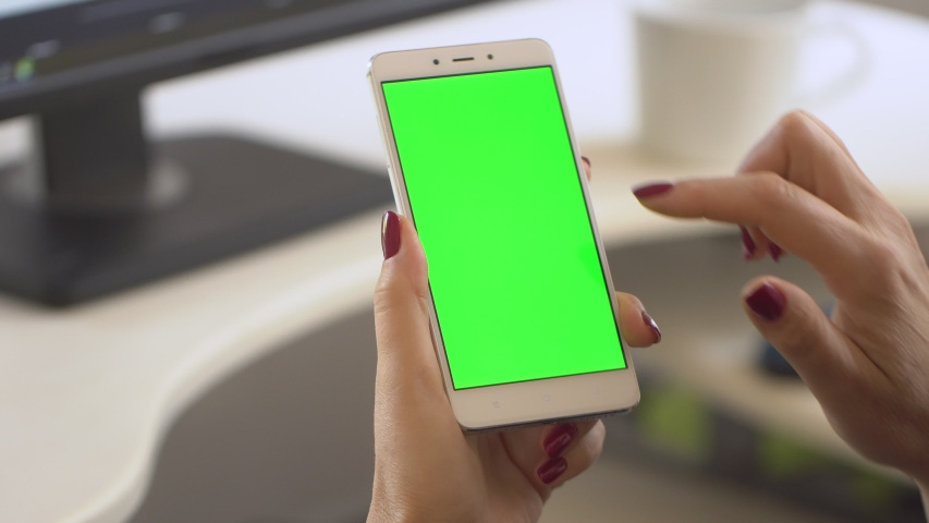 Business woman using smartphone viewing green screen on mobile phone browsing chroma key online watching enjoying drinking coffee reading social media close up hands | Shutterstock HD Video #1037210150