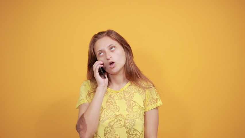 Brunette girl in yellow t-shirt over isolated orange background shows emotions | Shutterstock HD Video #1037217704