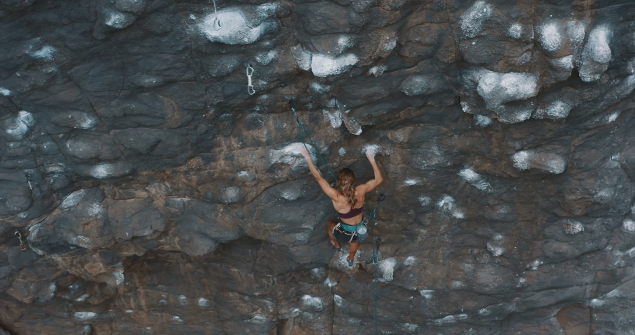 Aerial drone view of young fit woman lead rock climbing on an outdoors sport route, fast experienced rock climber