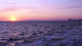 Video of sunset seen from fast moving boat in Izmir in Turkey. Scenic pink sky 4K resolution in motion video. Aegean sea at sunset. Looking at beautiful sunset sky from moving boat. Push the boat out