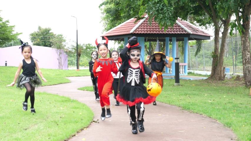 Group of asian children in halloween costume running in park.   Shutterstock HD Video #1037237399