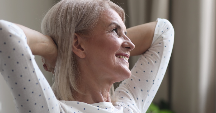 Happy relaxed dreamy middle aged older woman relax hold hands behind head sitting at home, calm mature adult lady smiling face rest dream alone enjoy comfort stress free peace of mind, close up view