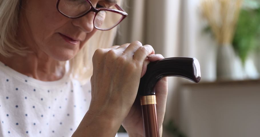 Upset old senior woman hold cane stick feel sad depressed about health problem sit alone at home near window wait caregiver visit, frustrated grandmother worried of disease concept, close up view
