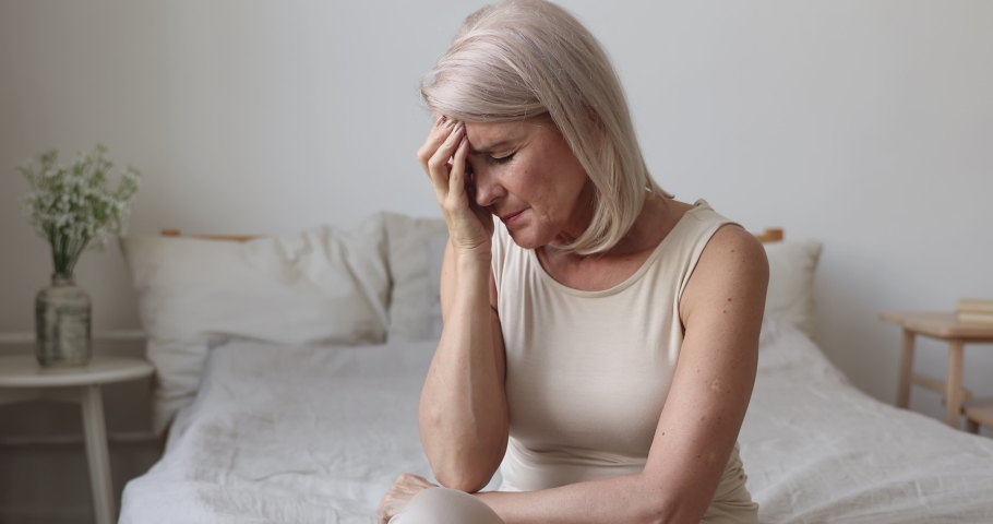 Upset tired old mature woman feel pain coping with morning headache concept, fatigued dizzy frustrated senior middle aged lady touch head suffer from migraine vertigo high blood pressure sit on bed