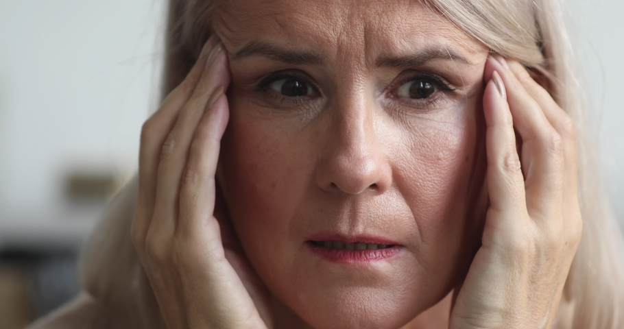Close up view of scared upset middle aged older woman feeling afraid stressed face thinking of disease or mental problems having strong headache suffer from panic attack or memory loss concept