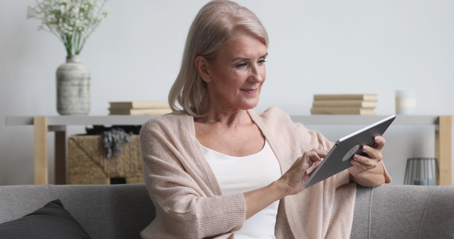 Smiling middle aged old woman relaxing holding digital tablet reading e book sit on sofa at home, senior adult lady enjoying using computer pad apps browsing internet shopping on couch in living room
