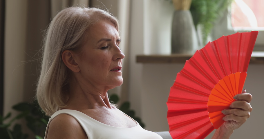 Overheated old senior woman feel hot wave fan annoyed with high temperature sit at home, stressed middle aged lady sweating suffer from climax summer weather heat problem without no air conditioner