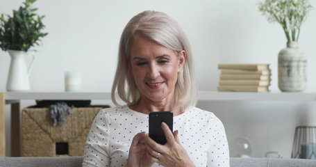 Happy middle aged mature woman holding smart phone looking at cellphone screen playing mobile games using social media apps in smartphone sit on couch at home, older people and technology concept