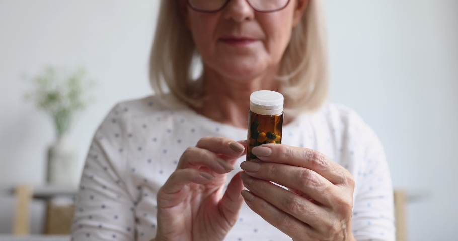 Sick ill old senior woman hold painkiller pill bottle read prescription side effect take medicine meds to relieve pain in mature grandma hands, older people pharmacy medicament concept, close up view