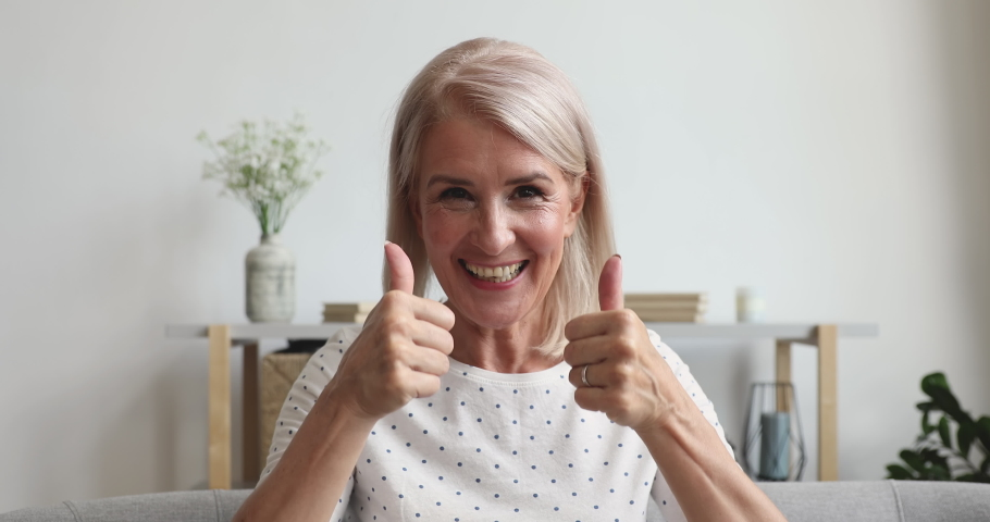 Happy middle aged old woman talking to camera sit on sofa at home, smiling senior retired adult lady blogger waving hand looking at webcamera doing video conference chat calling online, webcam view