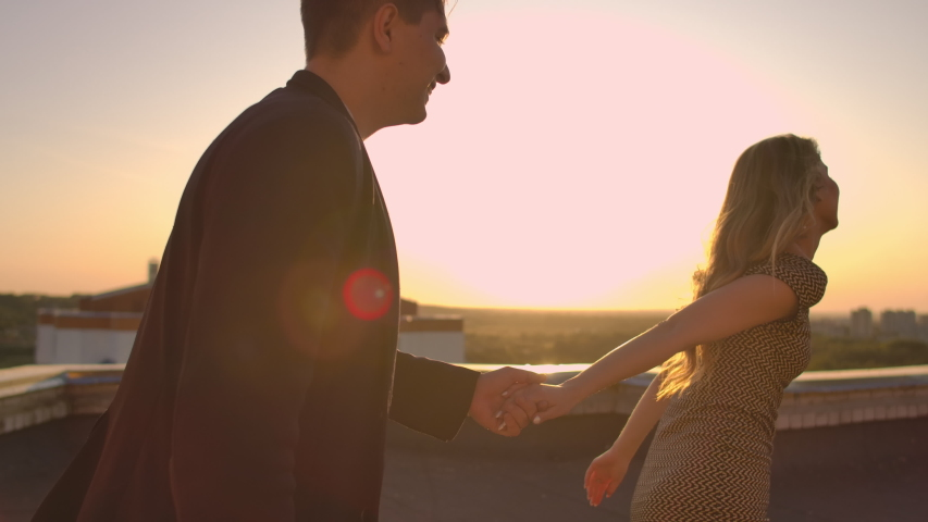 Young couple holding hands walking woman leading boyfriend the roof of the building at sunset POV travel concept. Carefree free lovers run on the roof laughing and smiling.