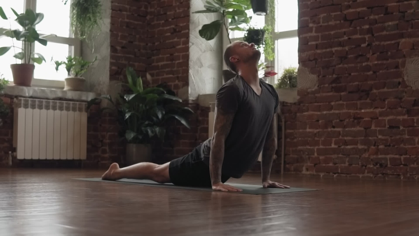 Man practice yoga pose in studio with brick wall. Fitness and healthy lifestyle concept. Attractive male making yoga pose in gym in slow motion. | Shutterstock HD Video #1037281205