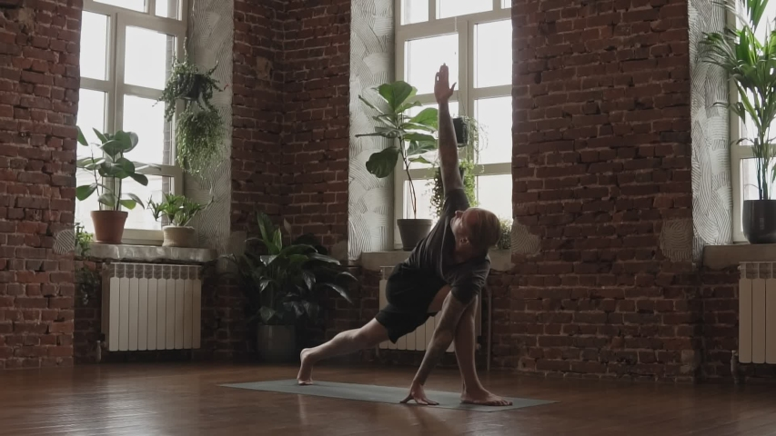 Yogi master workout on black mat in urban studio. Guy doing yoga indoors near windows. Young man doing asana in slow motion. Healthy lifestyle concept | Shutterstock HD Video #1037281256