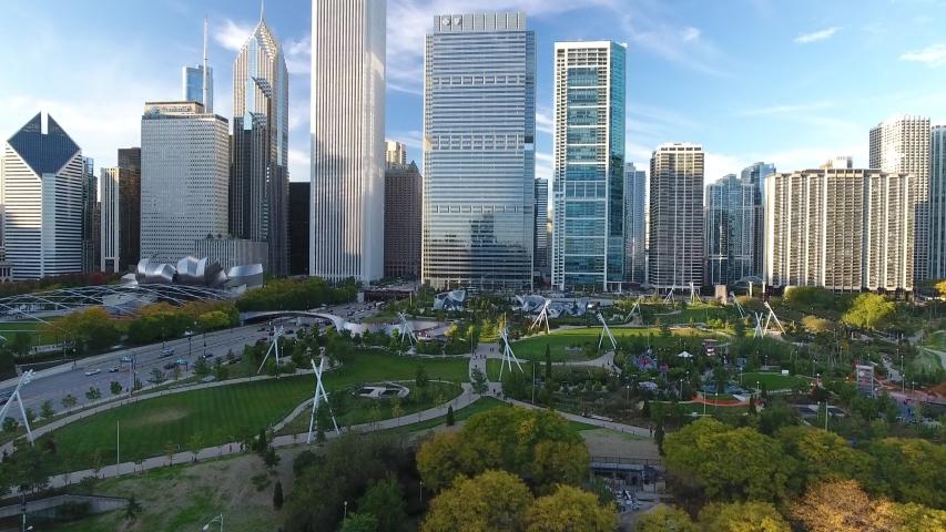 Millennium Park, Chicago, USA: Aerial drone shot view rising up over Millennium Park with Chicago buildings skyline at sunset