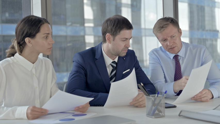 Executive Business people Discussing things through Documents on Office Table #1037296418