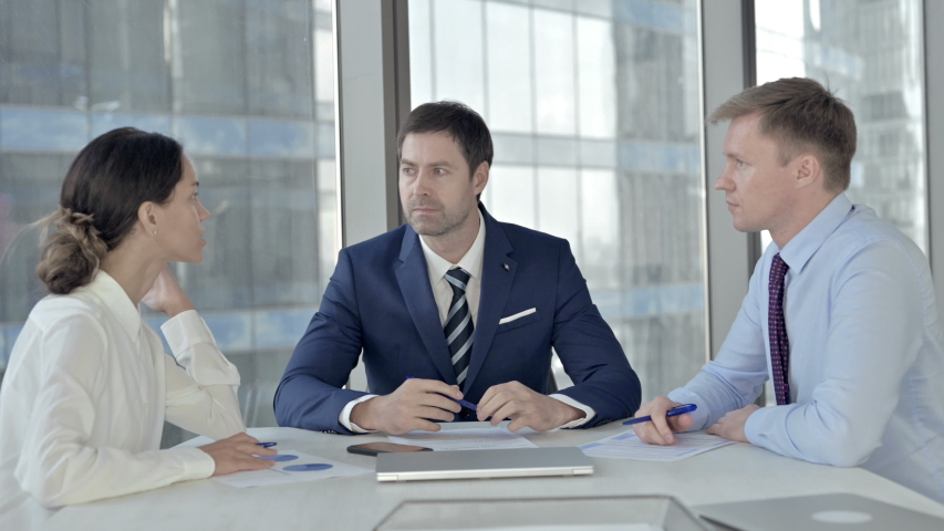 Middle Aged Businessman having Meeting with Assistants at Boardroom Table #1037296421