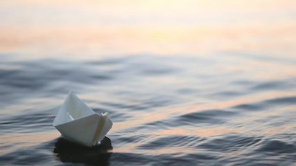 A paper boat is floating on the waves in the water at a beautiful sunset. Origami ship Sailing. The concept of a dream, future, childhood, freedom or hope. Slow motion
