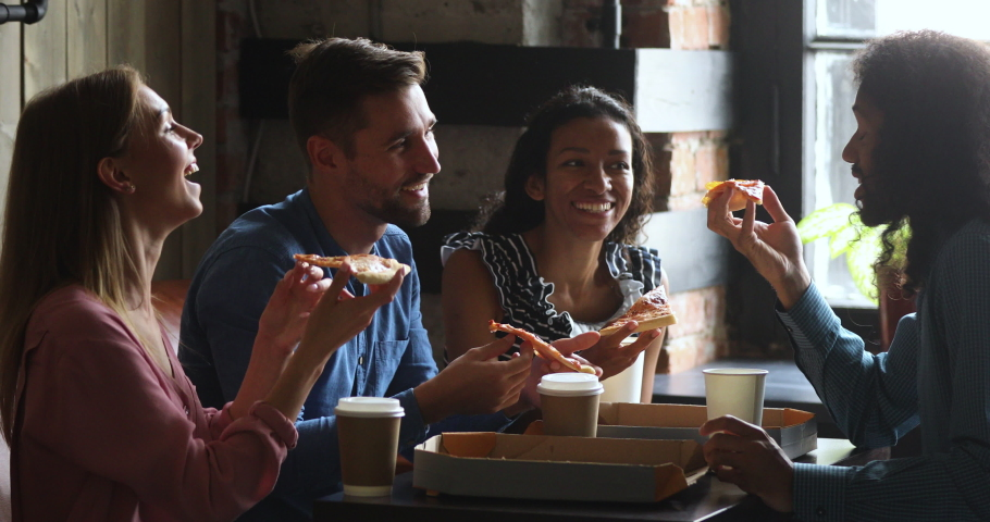 Happy multiracial business team people students laughing eating takeaway pizza together in cafe indoor, cheerful diverse staff friends group having fun share lunch food meal enjoy party sit at table Royalty-Free Stock Footage #1037298176