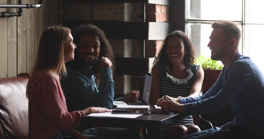 Happy multiracial diverse students or coworkers team study work together share cafe table talking laughing at funny joke having fun enjoy communication at group meeting in coffee shop room interior