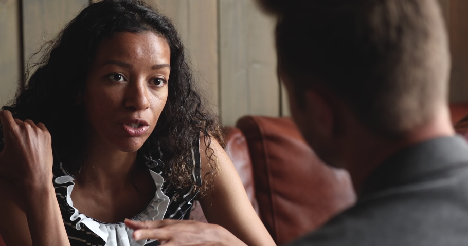 Young african american woman speaking to caucasian man at meeting indoors, two diverse female male friends colleagues couple talking relaxing communicating enjoy conversation on date or work break