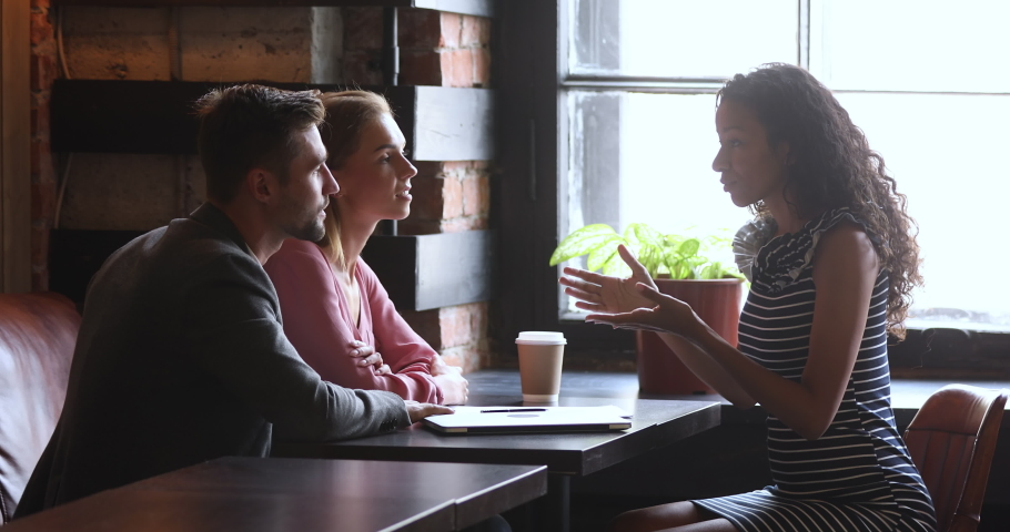 Female african manager broker saleswoman consult family customers make mortgage insurance loan offer, advisor agent insurer explain couple clients deal benefit convince buy service at meeting in cafe