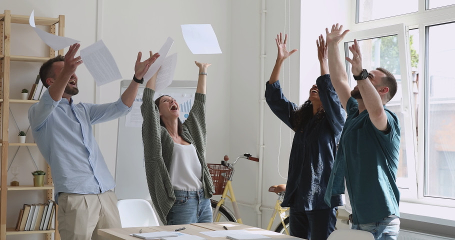 Excited motivated multiracial business team people staff group throw toss papers up stand at office table celebrate corporate success freedom at friday party enjoy victory dance having fun at work