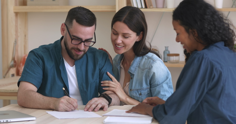 Happy excited young family couple customers clients sign mortgage investment contract sale purchase agreement deal handshake insurer agent take bank loan buy insurance service meeting broker realtor Royalty-Free Stock Footage #1037298266