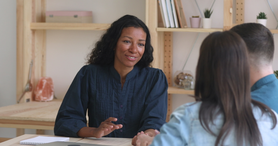 Female african bank manager broker realtor consult family customers make mortgage insurance loan offer, saleswoman insurer explain couple clients deal benefit convince buy service at business meeting