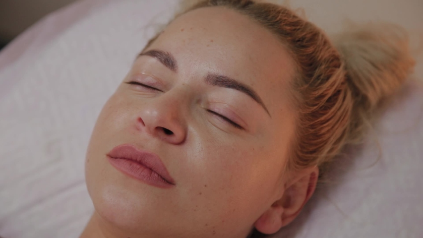 Beautiful young woman in bathrobe lying and waiting facial care procedure at luxury spa salon | Shutterstock HD Video #1037298521
