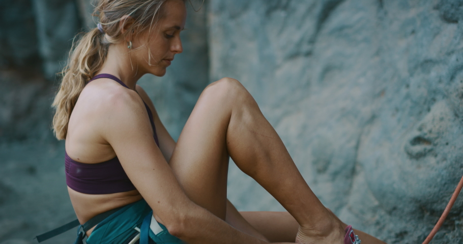 Fit woman putting on her rock climbing shoes preparing to rock climb, cinematic rock climbing moments