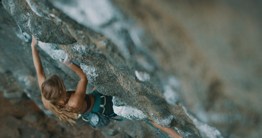 Strong fit woman rock climbing on tough sport route, rock climber makes a big move and falls
