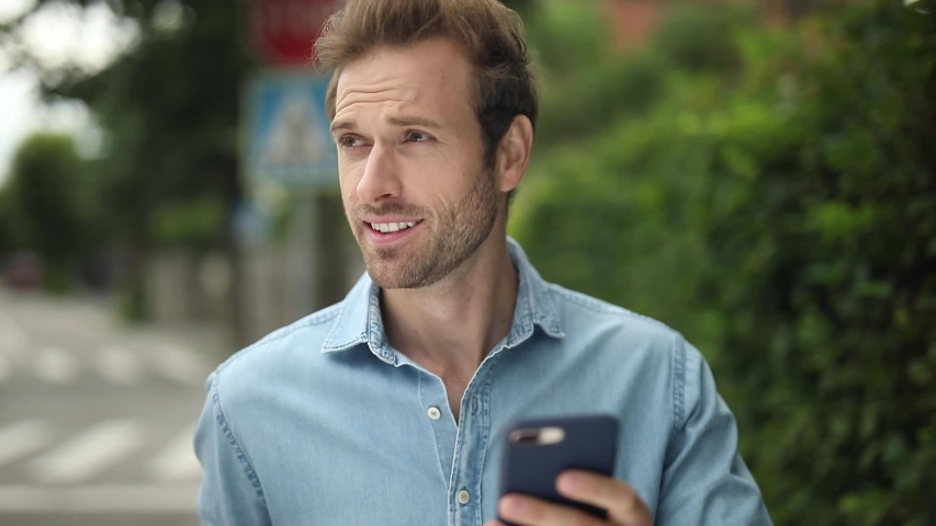 Young casual man walks and reads news on mobile phone and then looks to side and smiles | Shutterstock HD Video #1037301575