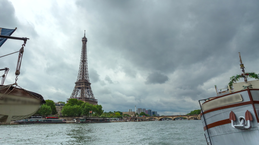 Eiffel Tower and river boats on the panoramic time lapse with cloudy sky in Paris, France. Summer cityscape, city life, vacation and touristic places in Europe.   Shutterstock HD Video #1037305349