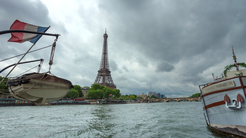 Eiffel Tower and river boats on the  time lapse with cloudy sky in Paris, France. Summer cityscape, city life, vacation and touristic places in Europe.   Shutterstock HD Video #1037305352