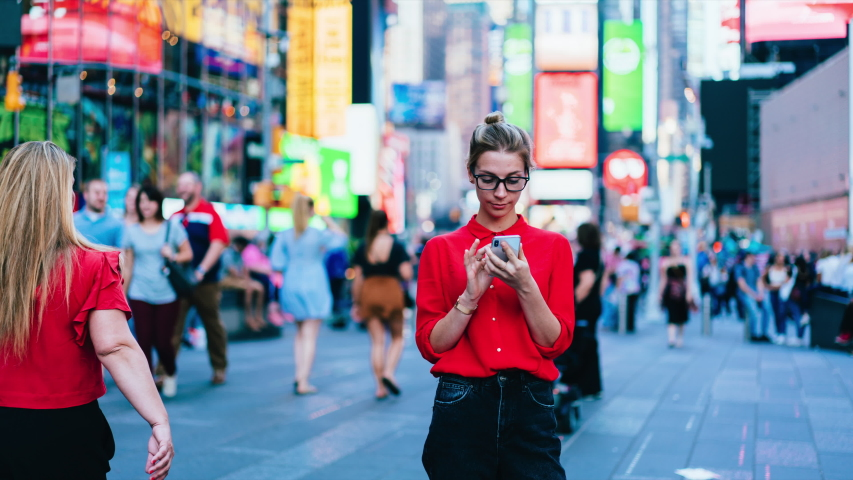 Time lapse effect of millennial female blogger in trendy clothing standing at crowd square with cellular phone for networking on websites ignoring life going near prefer mobile communication | Shutterstock HD Video #1037306342