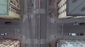 Empty street in Stockholm city, Sweden aerial top down view. Quarantined city, empty abandoned streets during corona virus outbreak. Drone shot flying over buildings, parked cars and street