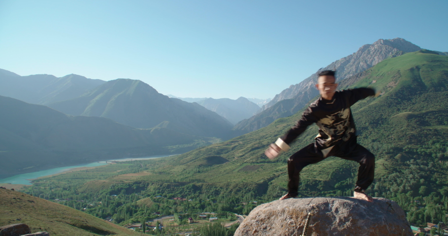 Asian in a black kimono engaged in martial arts in the mountains in the fresh air. Strong man masterfully owns karate | Shutterstock HD Video #1037326724