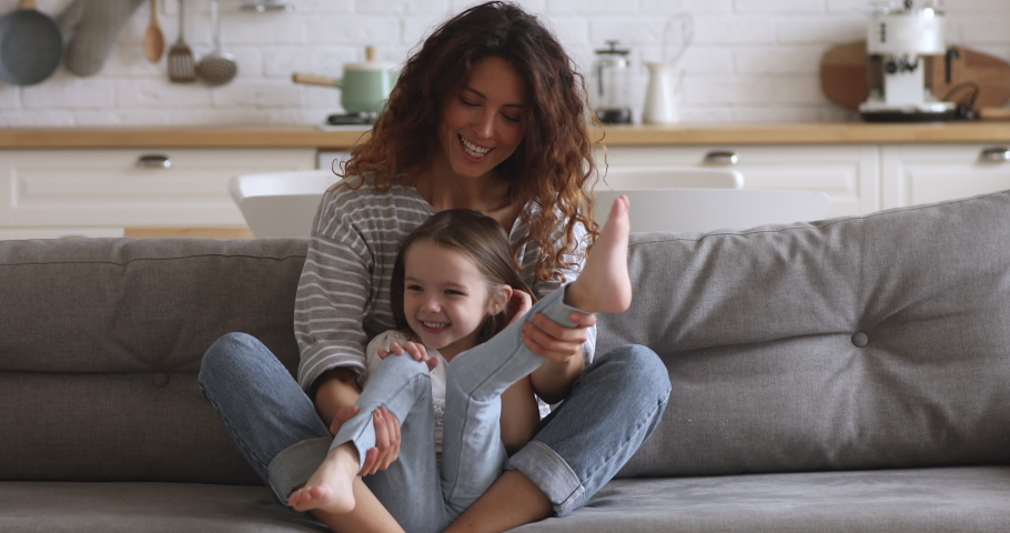 Happy family single young mum playing with small cute kid daughter laughing bonding together, loving mother having fun with little funny child girl cuddling tickling sitting relaxing on sofa at home #1037333354