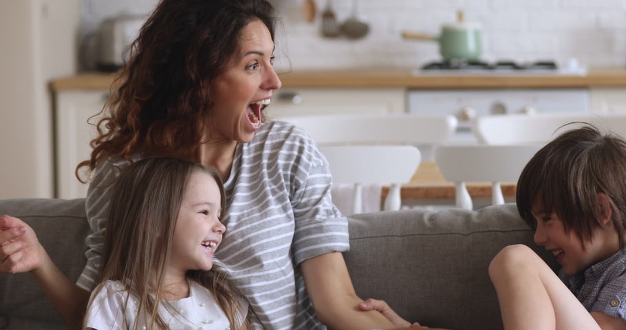 Happy family young mom having fun tickling small funny kids son daughter laughing together on couch, mother playing with little cute children at home relaxing cuddling sit on sofa in kitchen room | Shutterstock HD Video #1037333360