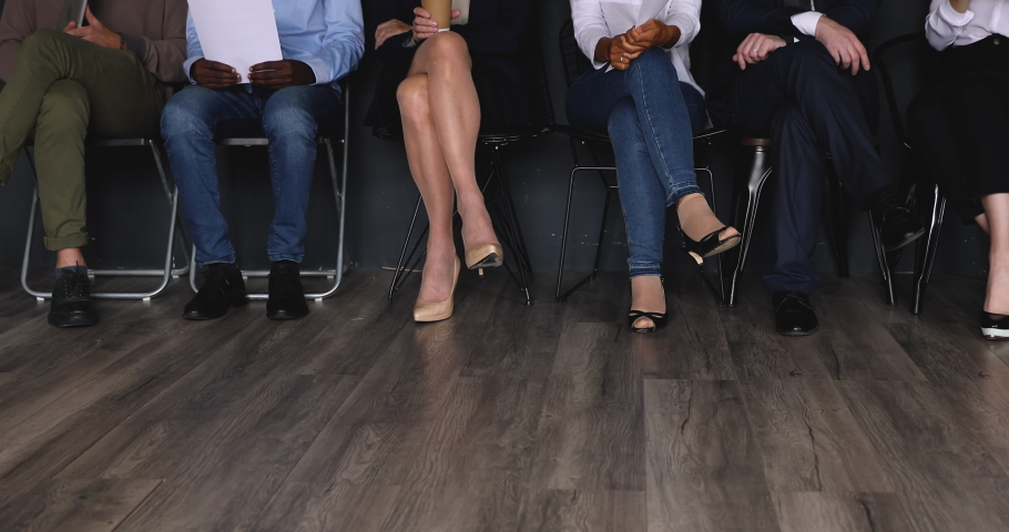 Diverse professional business people group sit on chairs in row line queue waiting for their turn on job interview, multiracial applicants legs close up view, human resources and recruitment concept | Shutterstock HD Video #1037333384