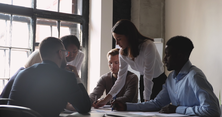 Serious female manager executive and diverse team people analyze paperwork talk work together gather at briefing table share ideas in teamwork discuss project plan at office group corporate meeting Royalty-Free Stock Footage #1037333420