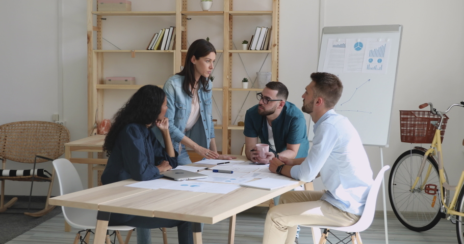 Multiracial business team people and female corporate leader work together on paperwork, businesswoman boss explain project result talk training diverse staff gather at modern office meeting table Royalty-Free Stock Footage #1037333432